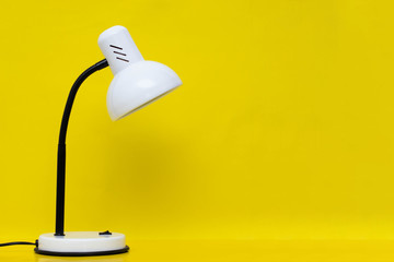 White table lamp on a yellow background. Free space for text.