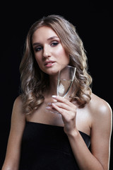 Girls with glass of champagne in hand. Beautiful young woman with vogue shining sparkle face makeup