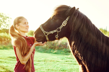 young beautiful girl strokes horse