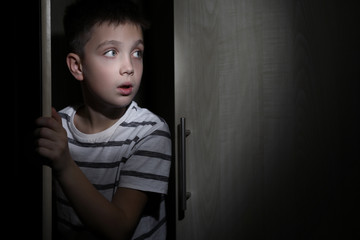 Scared little boy hiding in wardrobe. Domestic violence concept