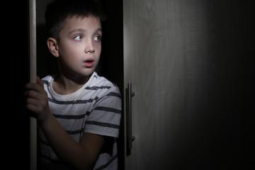 Scared little boy hiding in wardrobe. Domestic violence concept