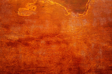Closeup of a sheet of an obsolete abandoned rusty fiery red metal with spots, scratches and other damage. Abstract, trendy, modern, texture background with copy space for text. Wall mural
