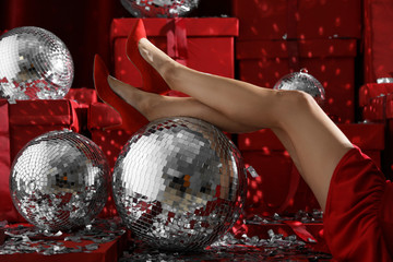 Woman sitting near disco balls on red Christmas gifts indoors, closeup