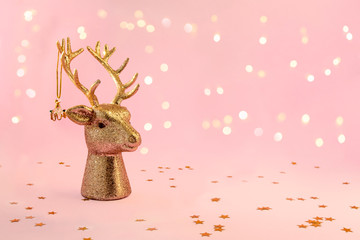 Xmas composition in minimal style - golden deer head with christmas bauble hanging on horns on pink background with New Year lights, copy space