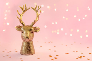 Christmas composition in minimal style - golden deer head on pink background with New Year lights, copy space