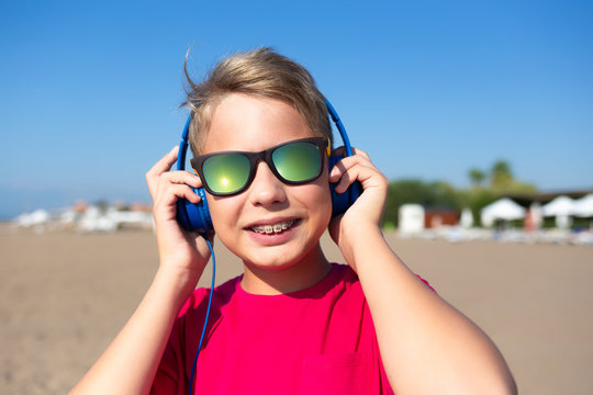 Closeup portrait of cute sunshine happy young kid smiling cheerfully. Teeth with modern braces. Boy wearing sunglasses and blue headphones. Horizontal color photography.