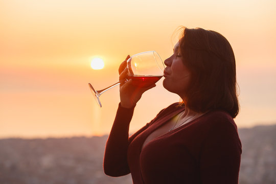 Woman with red wine on sunset mountains, close up of hand holding glass of wine. Elegant woman enjoying beautiful mountain ans sea landscape on sunset.