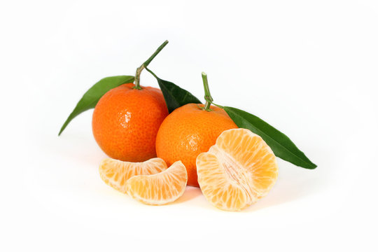 Fresh corsican clementines with green leaves and juicy slices isolated on white background