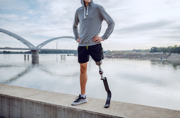 Fotomurales - Fit healthy Caucasian handicapped man in sportswear and with artificial leg standing on quay with hands on hips.