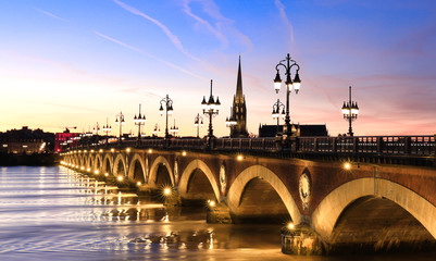 Photo sur Toile Con. Antique View of the Pont de pierre with sunset sky scene which The Pont de pierre crossing Garonne river,