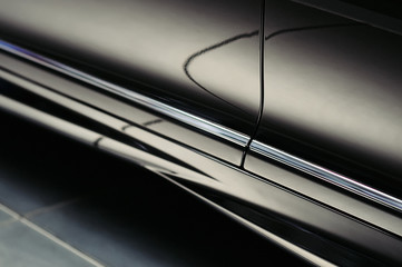 Closeup door of a modern luxury black car with beautiful reflections. Exterior details. Abstract shiny dark chrome surface with cute reflections