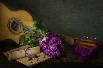Still life with lilac branch and guitar