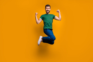 Full length photo of cheerful crazy funky guy jump win lottery show his strength biceps triceps raise fists scream yeah wear green t-shirt isolated over yellow color background