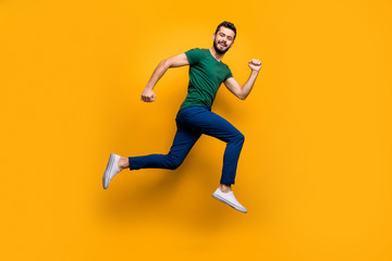 Full size photo of cheerful guy jump run fast for discounts wear modern clothing isolated over yellow color background