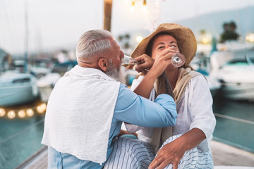 Senior couple date drinking champagne on sailboat vacation - Happy elderly people having fun celebrating wedding anniversary on boat trip - Relationship love and romantic travel dating concept