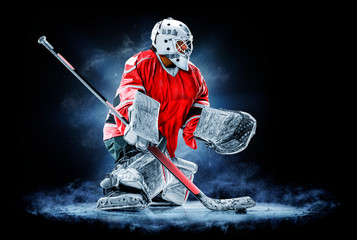 Professional ice hockey goalkeeper or goalie or goaltender isolated on black backgroung