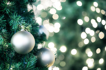 Closeup of blond bauble hanging from a decorated christmas tree on blurred of lights with decorated...