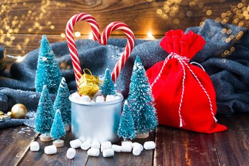 Christmas marshmallows and new year decorations on wood background with grey plaid. Winter holidays