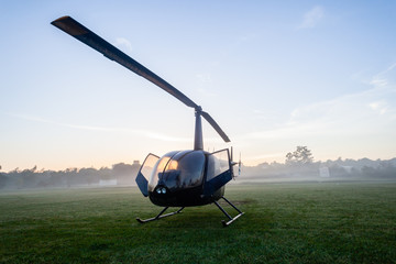 Foto op Plexiglas Helicopter Helicopter Four Seater Aircraft Parked Dawn Grass Field