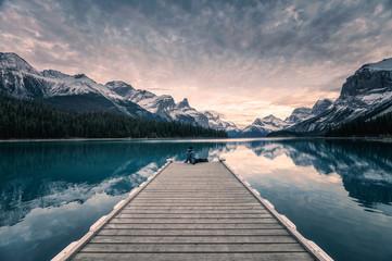 Spoed Fotobehang Grijs Traveler relaxing on wooden pier in Maligne lake at Spirit island, Jasper national park