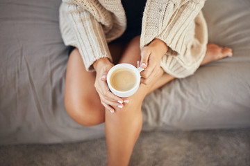 Papiers peints The Top view of caucasian woman dressed in beige sweater sitting on bed and holding fresh morning coffee.