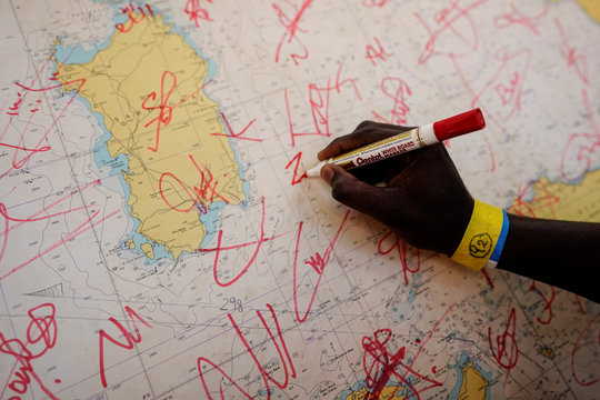 A migrant signs a nautical chart for the crew of NGO Proactiva Open Arms rescue boat in central Mediterranean Sea