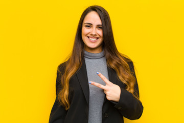 young pretty woman feeling happy, positive and successful, with hand making v shape over chest, showing victory or peace job or business concept