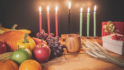 Foto op Canvas Afrika Kwanzaa holiday concept with decorate seven candles red, black and green, gift box, pumpkin,corn and fruit on wooden desk and background.