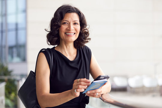 Portrait Of Mature Businesswoman With Passport In Airport Departure Lounge Using Mobile Phone