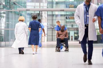 Female Nurse Wearing Scrubs Wheeling Patient In Wheelchair Through Lobby Of Modern Hospital Building