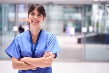 Portrait Of Female Doctor Wearing Scrubs Standing In Modern Hospital Building