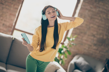 Portrait of positive cheerful girl enjoy music she listen on blue wireless headset find on...