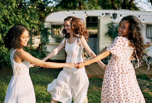 Three smiling women dancing in circle during picnic