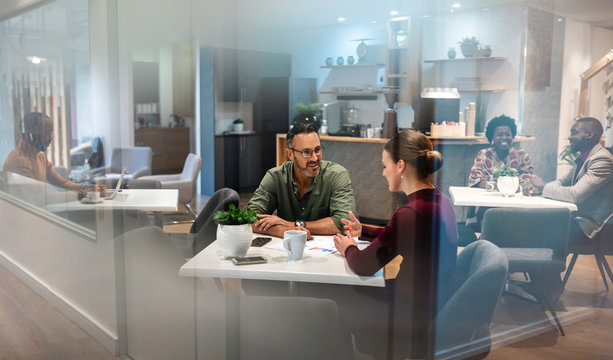 Wide shot of office canteen. Woman being interviewed by male employer. Background candid people