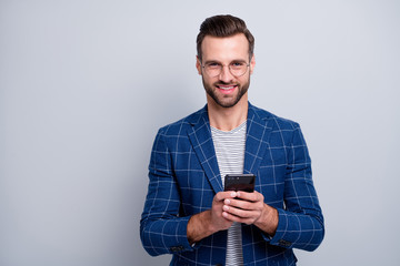 Photo of cheerful positive handsome man smiling toothily browsing through telephone having free time fun during business conference isolated grey background