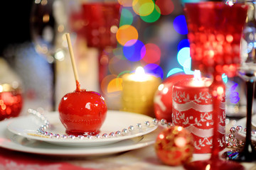 Beautiful table setting for Christmas party or New Year celebration at home. Cozy room with a fireplace and Christmas tree in a background.