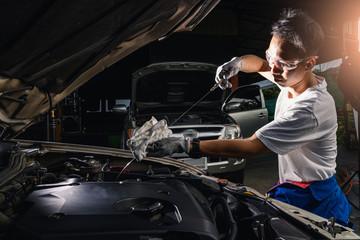 The abstract image of the technician checking the level of engine lubricant. the concept of automotive, repairing, mechanical, vehicle and technology.