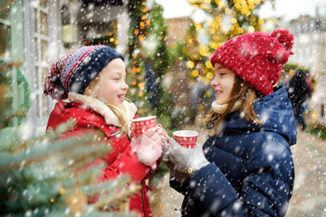 Two adorable sisters drinking hot chocolate on traditional Christmas fair in Riga, Latvia. Children enjoying sweets, candies and gingerbread on Xmas market.