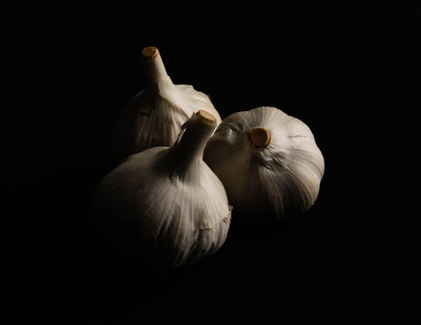 White garlic bulbs isolated on a black background