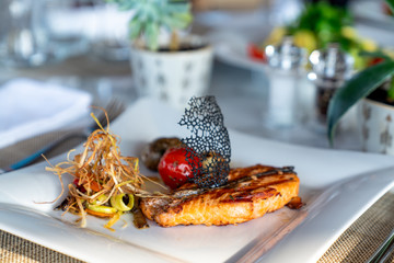 A delicious roasted salmon is served in a elegance restaurant or hotel