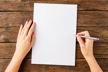Woman's hands writing with pen over blank white paper sheet on wooden table. Top view