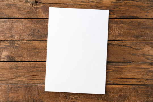 Empty white paper sheet on rustic wooden table. Top view
