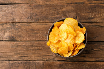 Tasty potato chips in bowl on rustic wooden background with copyspace. Top view