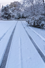 Tire tracks in snow on driveway in winter