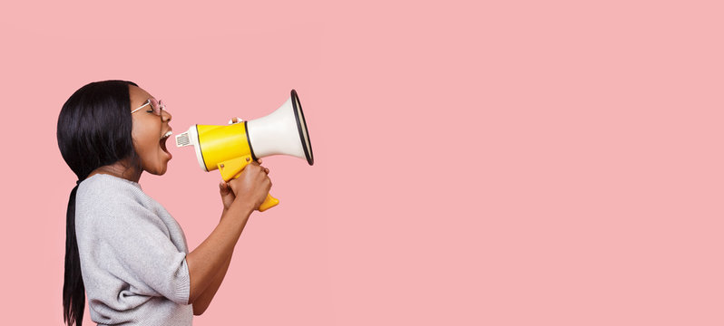 Young woman shouting in megaphone over pink background
