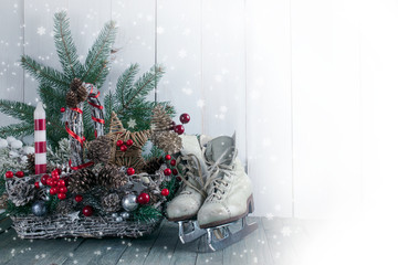 Christmas background with wicker basket, skates for figure ice skating, fir tree on wooden old shabby table, New Year holiday rustic home interior decor.
