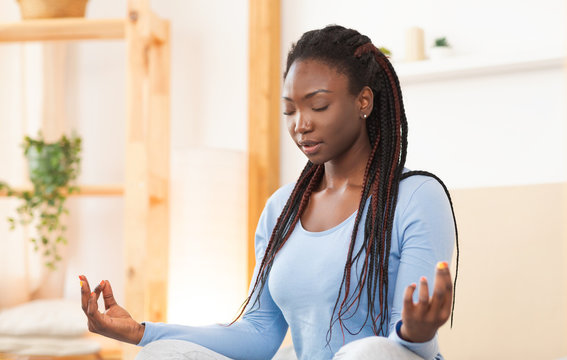 Young Black Woman Meditating In Lotus Position In Bed Indoor