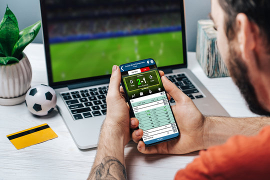 Man making bets online using mobile application on his phone