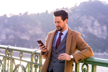 An elegant man standing on a bridge and using his smartphone