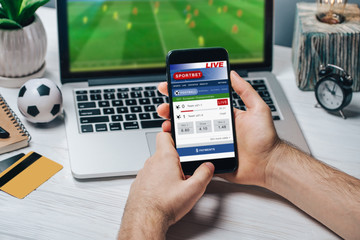 Cropped shot of male fan making bets using gambling mobile application on his phone